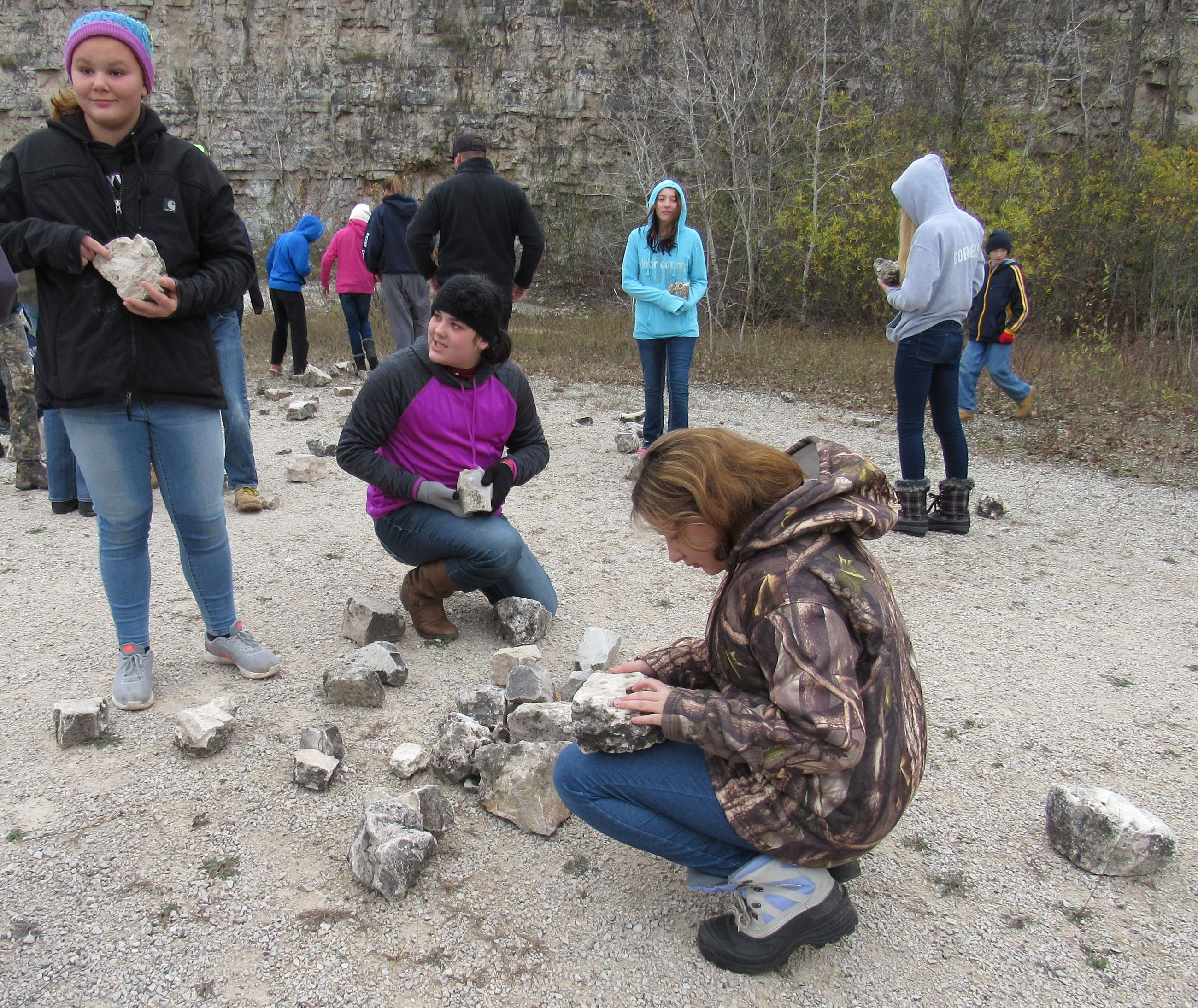 Teens looking at rocks with fossils in them in a quarry