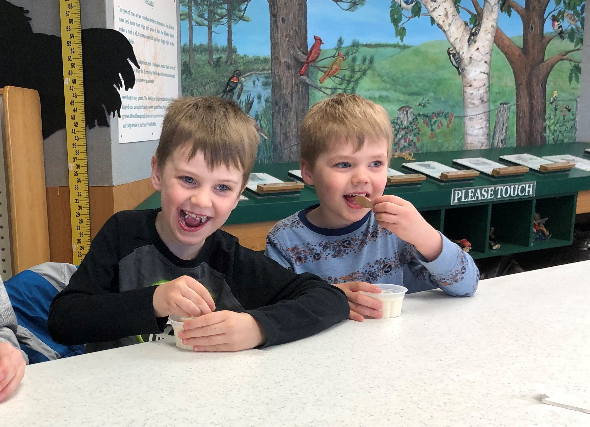 two boys eating ice cream with maple syrup on it