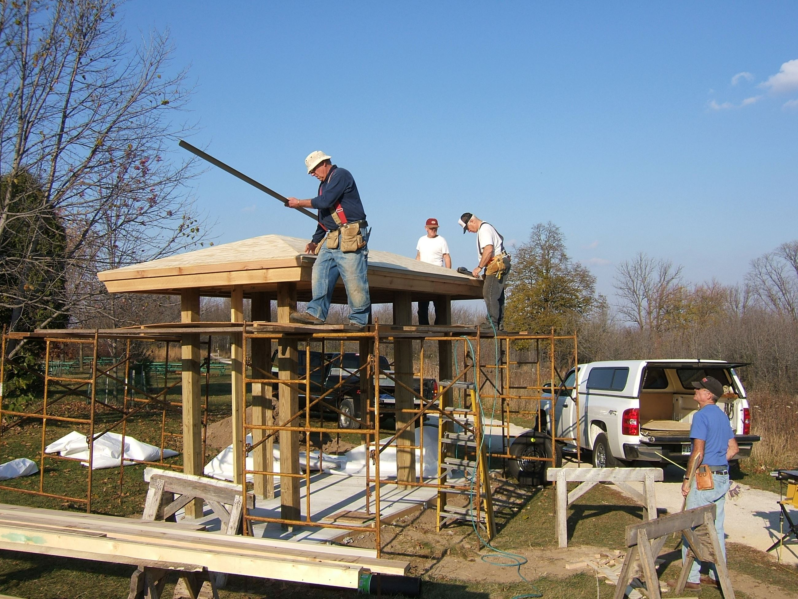 Four me building a kiosk. 3 are standing on scaffolding and working on the roof, 1 is on the ground