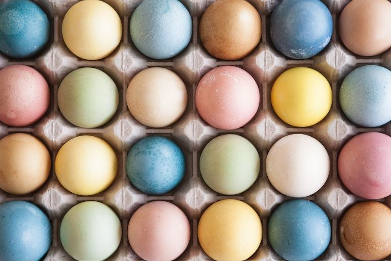 Different colored eggs in a carton, all the colors are earthy natural tones.